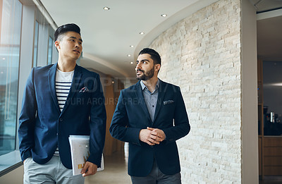 Buy stock photo Shot of two young businessmen walking and talking in a modern office