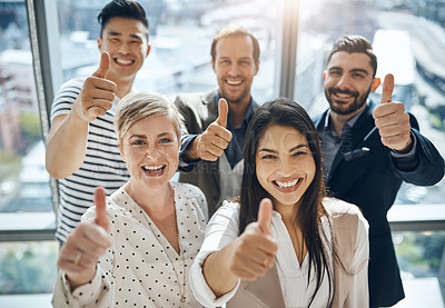 Buy stock photo Portrait of a group of confident young businesspeople standing together while showing thumbs up inside of the office during the day
