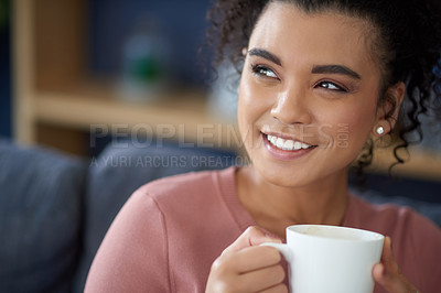 Buy stock photo Cropped shot of an attractive young woman enjoying a cup of coffee while relaxing on her sofa at home