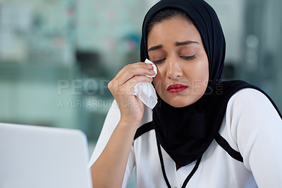 Buy stock photo Shot of a young businesswoman crying at her desk in a modern office