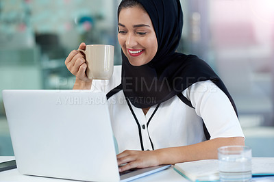 Buy stock photo Shot of a young businesswoman using a laptop and having coffee in a modern office