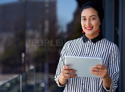Buy stock photo Shot of a young businesswoman using a digital tablet on the balcony of a modern office