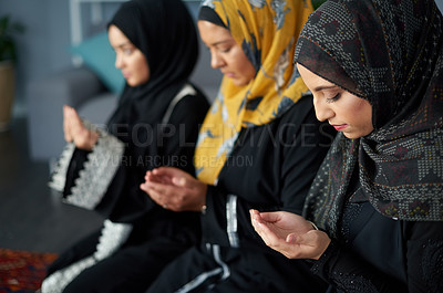 Buy stock photo Shot of a group of young muslim women praying together indoors