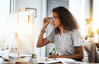 Buy stock photo Cropped shot of a businesswoman adjusting her glasses while working on her computer