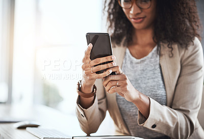 Buy stock photo Shot of a businesswoman using her cellphone while sitting at her desk