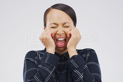 Buy stock photo Studio shot of a young woman crying while standing against a gray background