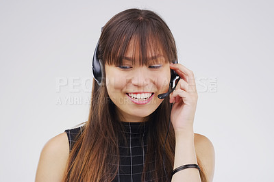 Buy stock photo Studio shot of an attractive young female customer service representative wearing a headset against a grey background