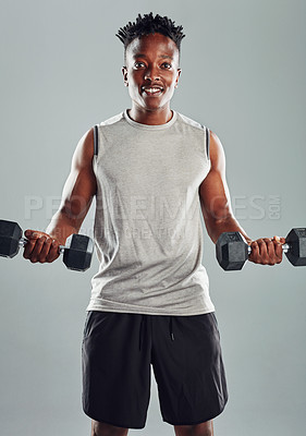 Buy stock photo Studio shot of a sporty young man working out with dumbbells against a grey background