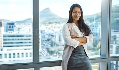 Buy stock photo Portrait of a confident young businesswoman posing with her arms folded in her office