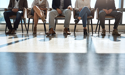 Buy stock photo Shot of a group of unrecognizable businesspeople sitting in line in an office