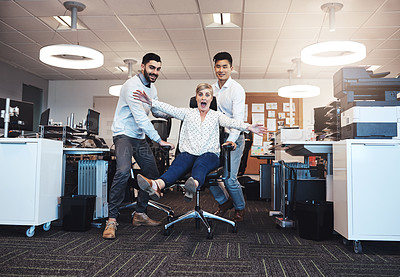 Buy stock photo Cropped shot of three businesspeople having fun by taking their colleague for a ride in her chair in the office