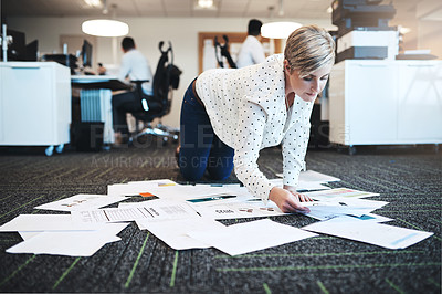 Buy stock photo Full length shot of an attractive young businesswoman working with paperwork on the floor in the office