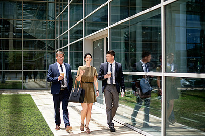 Buy stock photo Full length shot of three cheerful  businesspeople walking together outside an office building