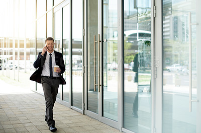 Buy stock photo Full length shot of a handsome businessman taking a phone call while walking outside an office building