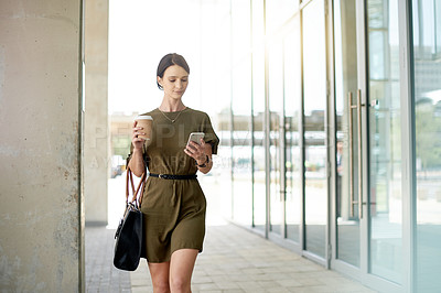 Buy stock photo Shot of a beautiful young businesswoman using her cellphone while walking outside an office building