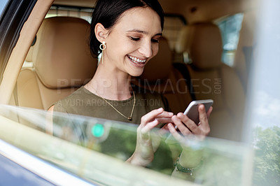 Buy stock photo Shot of a beautiful young businesswoman using a cellphone while sitting in the backseat of a car