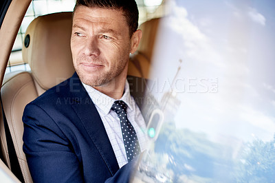 Buy stock photo Shot of a handsome businessman looking out the window while sitting in the backseat of a car