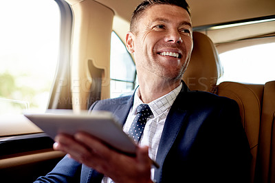 Buy stock photo Shot of a handsome businessman using a digital tablet while sitting in the backseat of a car