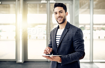 Buy stock photo Cropped portrait of a handsome young businessman using a tablet while standing in his office