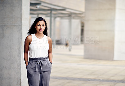 Buy stock photo Cropped portrait of an attractive young businesswoman standing with her hands in her pockets outside