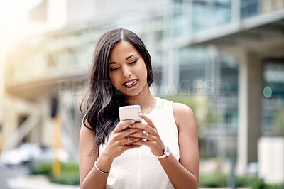 Buy stock photo Cropped shot of an attractive young businesswoman sending a text message while standing outside in the city
