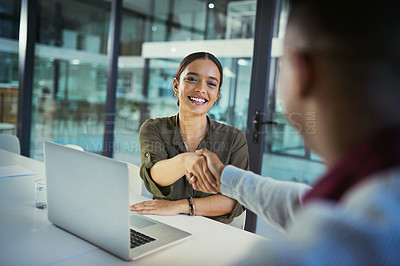 Buy stock photo Shot of a young businesswoman and businessman shaking hands during a late night meeting at work