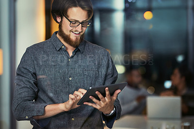 Buy stock photo Shot of a young businessman using a digital tablet during a late night at work