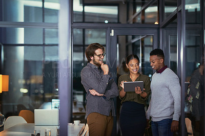 Buy stock photo Shot of a group of young businesspeople using a digital tablet together during a late night at work
