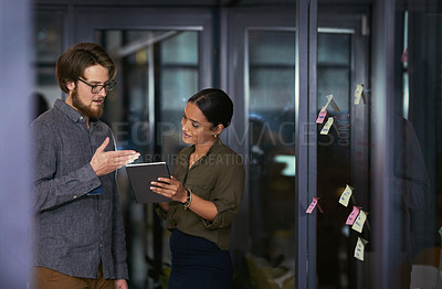 Buy stock photo Shot of a young businessman and businesswoman using a digital tablet together during a late night at work