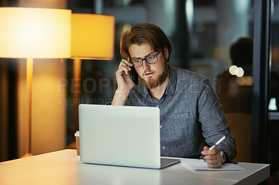 Buy stock photo Shot of a young businessman using a laptop and smartphone during a late night at work