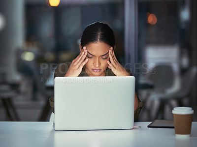 Buy stock photo Shot of a young businesswoman experiencing stress during late night at work