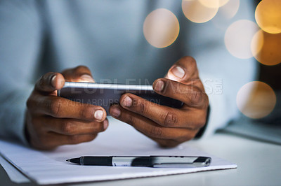 Buy stock photo Cropped shot of an unrecognizable businessman texting on his cellphone in the office at night