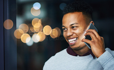 Buy stock photo Cropped shot of a cheerful young businessman talking on his cellphone inside the office during the night