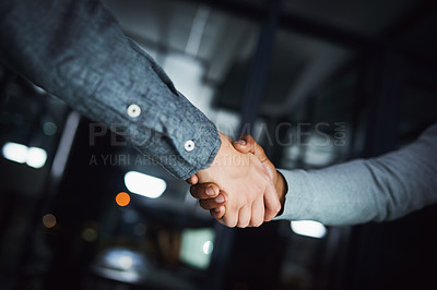 Buy stock photo Cropped shot of two unrecognizable businesspeople shaking hands in agreement inside of the office during the day