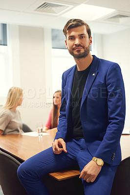 Buy stock photo Portrait of a handsome young businessman sitting on a office desk with his colleagues in the background