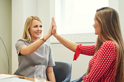Buy stock photo Shot of two young businesswoman high-fiving in an while working in their office