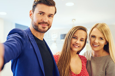 Buy stock photo Portrait of three young businesspeople taking a selfie together in an office
