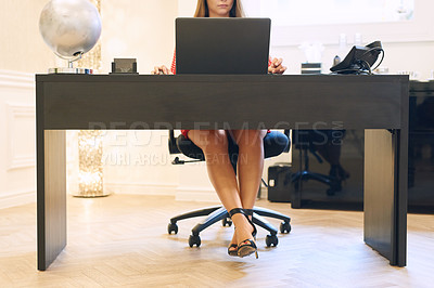 Buy stock photo Shot of an unrecognizable businesswoman working on a laptop at her office desk