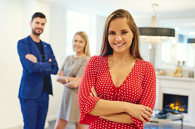 Buy stock photo Portrait of a beautiful young businesswoman posing with her arms folded in an office with her colleagues in the background