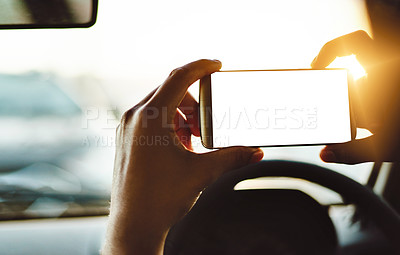 Buy stock photo Cropped shot of an unrecognizable woman photographing the view with her phone while driving