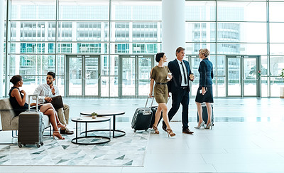Buy stock photo Shot of an busy airport with businesspeople walking to their flights or waiting inside during the day