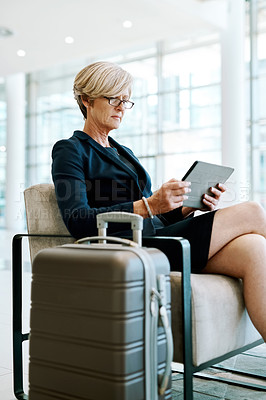 Buy stock photo Shot of a confident mature businesswoman seated with her luggage while browsing on a digital tablet inside of a airport during the day