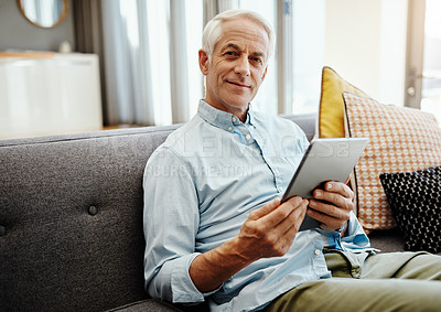 Buy stock photo Shot of a senior man relaxing and using a digital tablet on the sofa at home