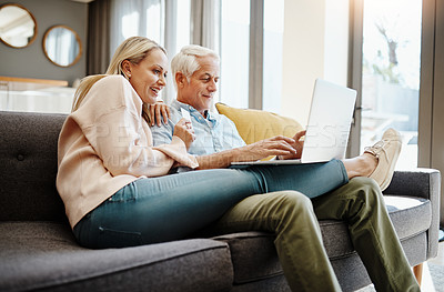 Buy stock photo Shot of a mature couple using a credit card and laptop on the sofa at home