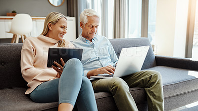 Buy stock photo Shot of a mature couple using a digital tablet and laptop on the sofa at home