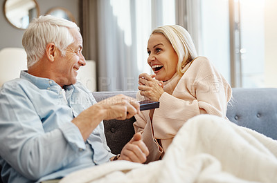 Buy stock photo Shot of mature man giving his wife a gift on the sofa at home