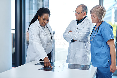 Buy stock photo Shot of a group of medical practitioners analyzing x-ray scans together