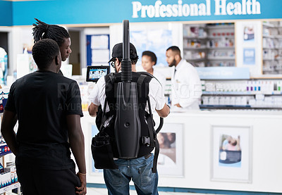 Buy stock photo Rearview shot behind the scenes of a camera crew shooting two pharmacists working inside of a pharmacy