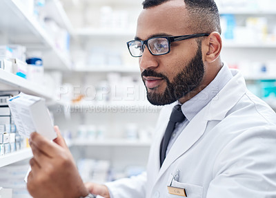 Buy stock photo Cropped shot of a confident young pharmacist working on a digital tablet inside of a pharmacy during the day