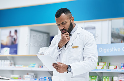 Buy stock photo Shot of a young pharmacist working on a digital tablet in a chemist